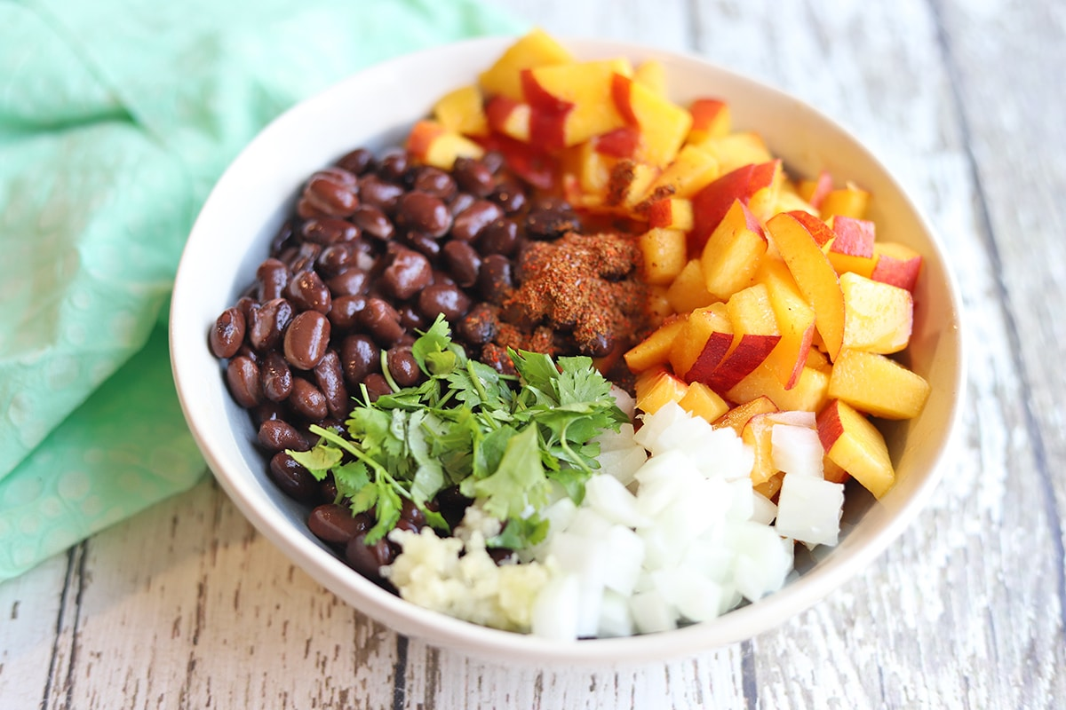 Bowl with peaches, onions, cilantro, beans, garlic, and spices.