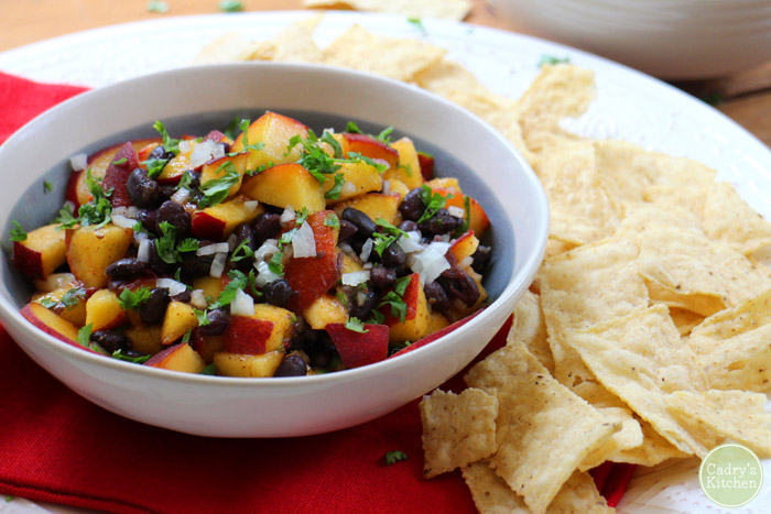 Peach and black bean salsa in bowl by pile of tortilla chips.