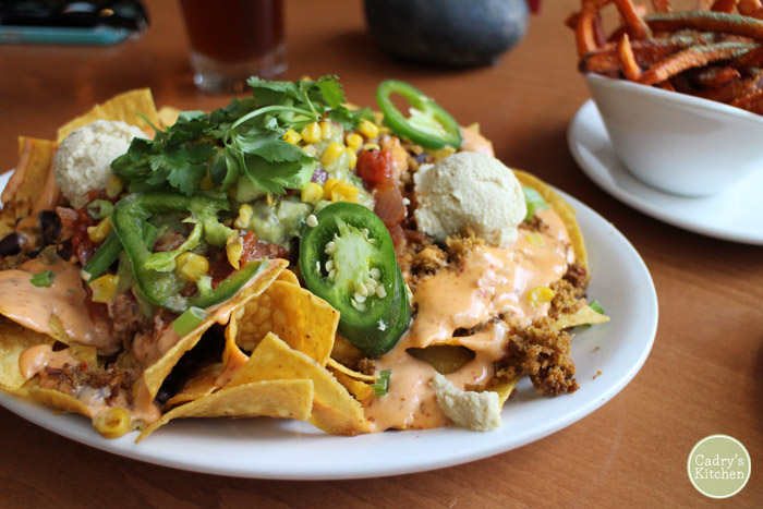 A huge pile of vegan nachos on plate.