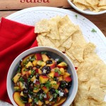 peach and black bean salsa in bowl with chips
