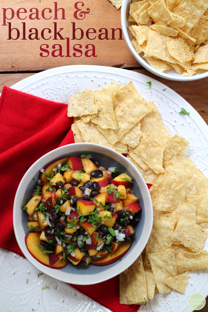 Text overlay: Peach and black bean salsa. Salsa in bowl by tortilla chips.