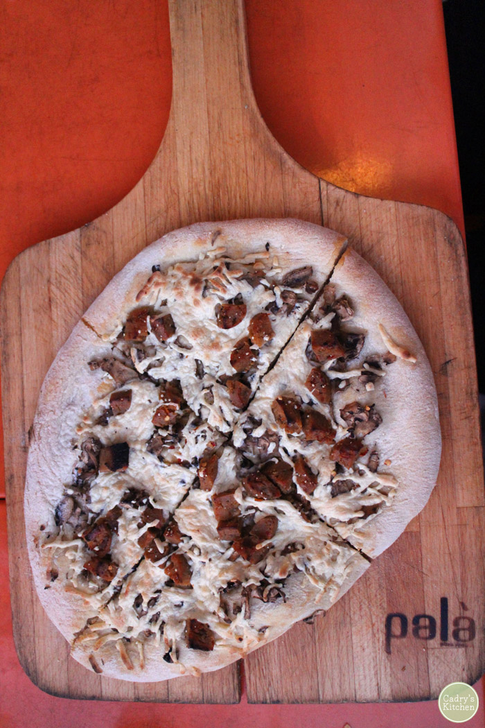 Sausage and mushroom pizza on wooden board.
