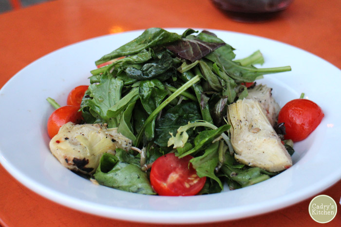 Salad with grilled artichokes and tomatoes in bowl.