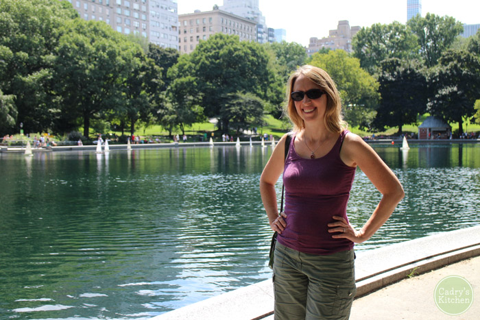 Cadry standing in Central Park with tiny sailboats floating on Conservatory Water.