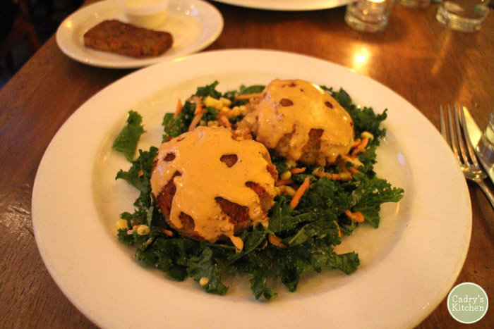 Vegan crab cakes on bed of kale.