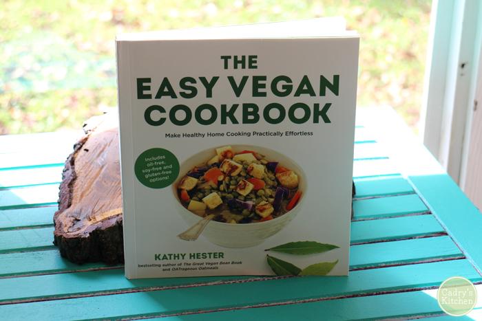 The Easy Vegan Cookbook on aqua table in front of window.