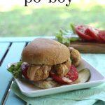 Text overlay: Spicy cauliflower po boy. Sandwich on plate by window.