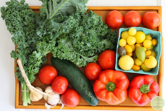 Tray with kale, tomatoes, bell peppers, garlic, and a cucumber.