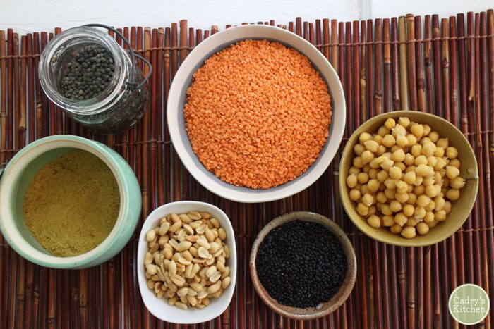 Red lentils, chickpeas, and beans in bowls.