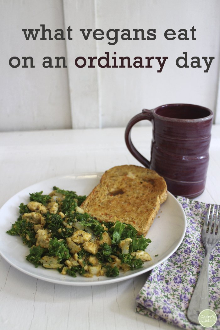 Text overlay: What vegans eat on an ordinary day. Tofu scramble on plate with toast by cup of coffee.