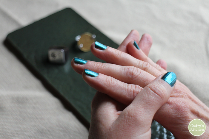 Hands folded together with bright blue polish.