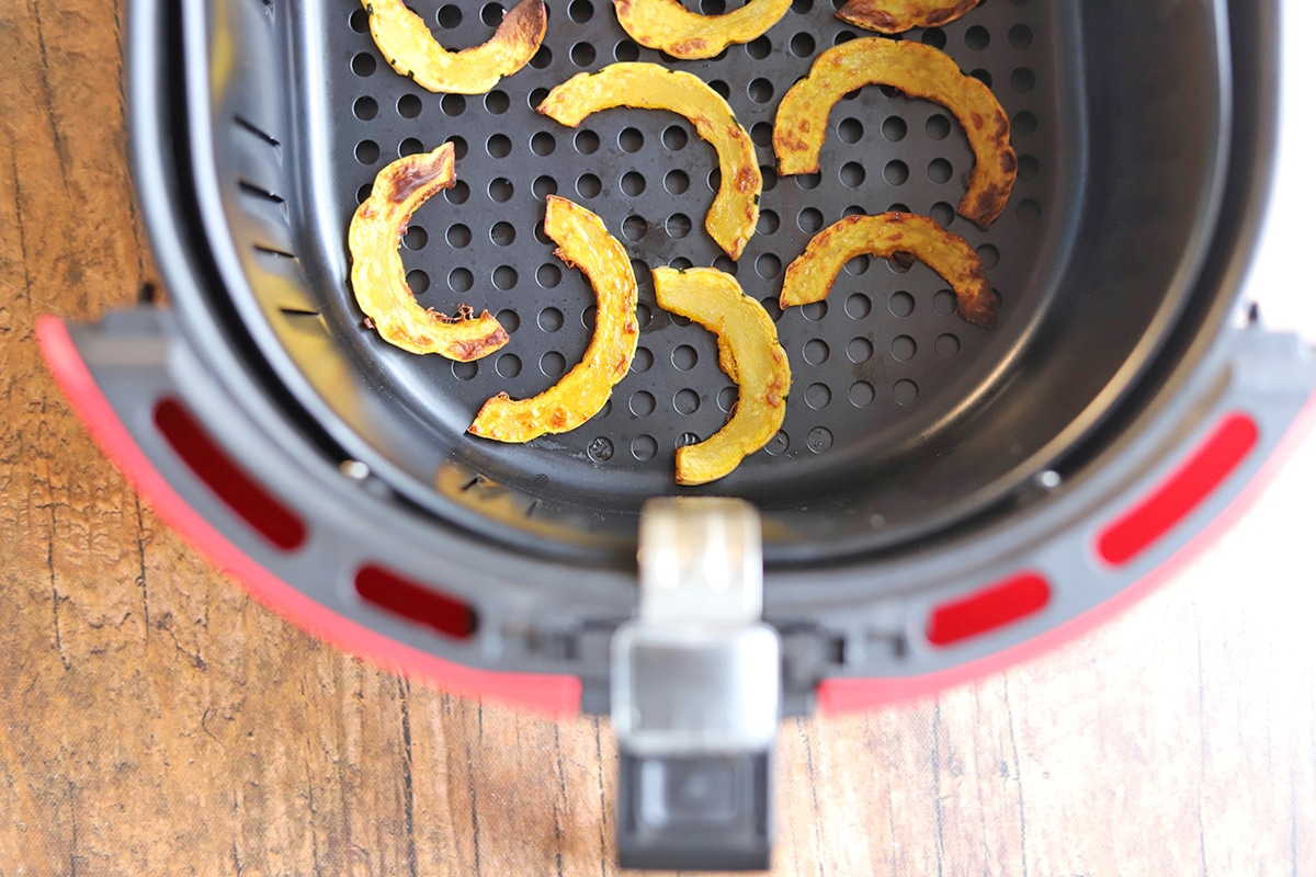 Slices of delicata squash in air fryer basket.