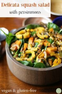 Text: Delicata squash salad with persimmons. Vegan and gluten-free. Bowl of squash salad with persimmons and caramelized onions.