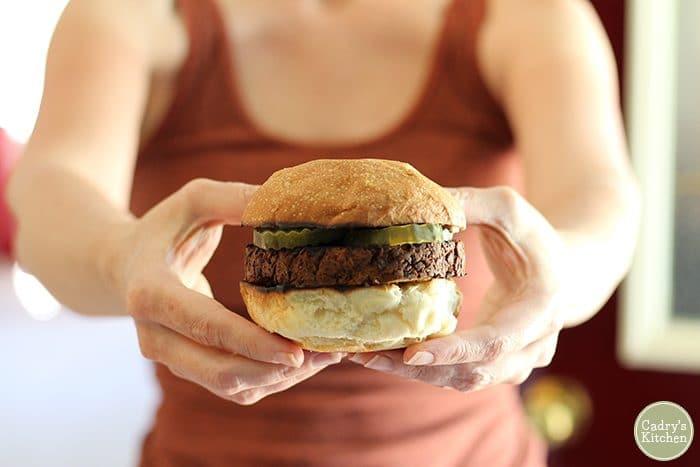 Hands holding Herbivorous Butcher vegan burger.