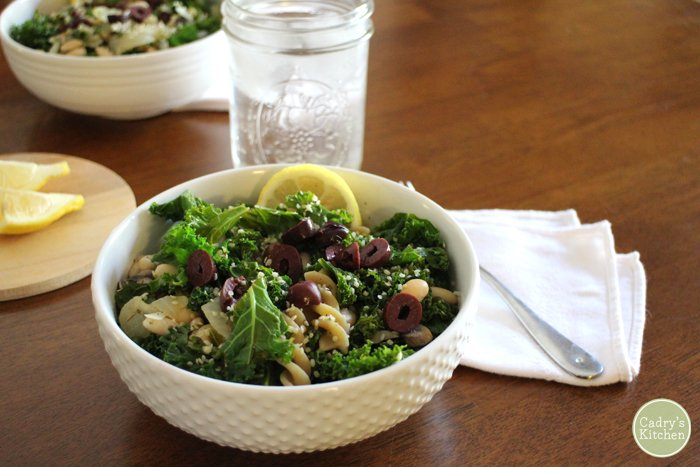 Pasta with kale and kalamata olives in bowl by glass of water.