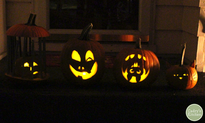 Carved jack o' lanterns lit up at night on the porch.