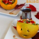 Jack o' lantern salad in carved orange on plate.