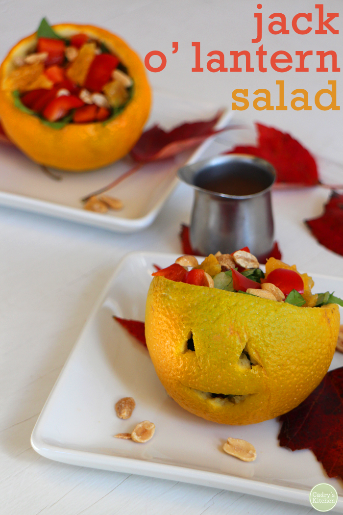 Text overlay: Jack o' lantern salad. Orange with face carved on it, on plate with peanut dressing.