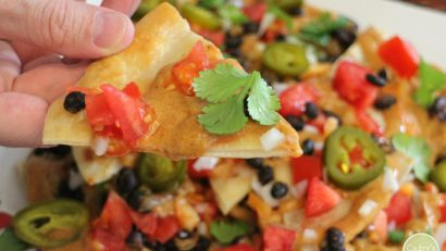 Hand holding puffy nacho with nut-free vegan queso.