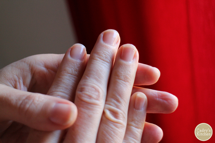 Fingernails with clear polish in front of red curtains.