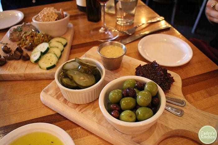 Olives, pickles, mustard, and fig jam on board at Brix.