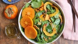 Overhead spinach salad with persimmons and roasted squash in bowl.