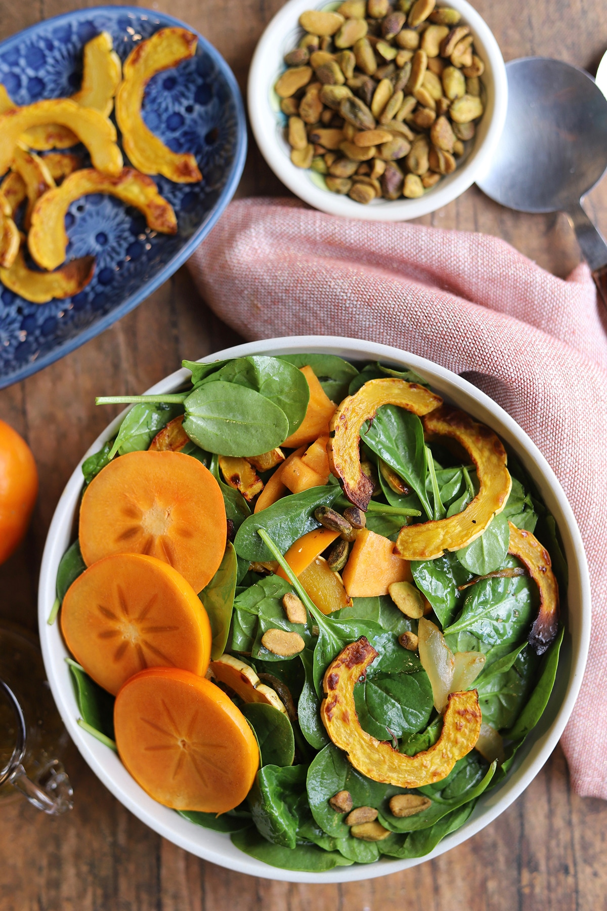Overhead salad in bowl by napkin, pistachios, and delicata squash.