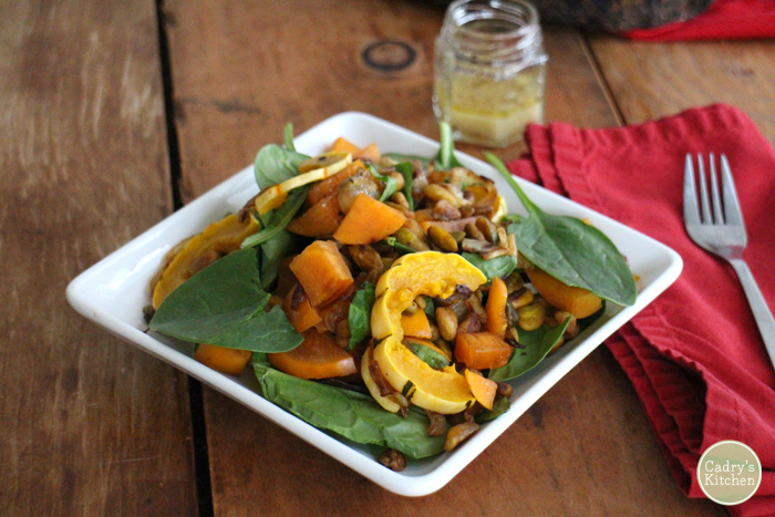 This delicata squash & persimmon salad highlights the flavors of fall. It's also a beautiful addition to your Thanksgiving table. | cadryskitchen.com #vegan #glutenfree