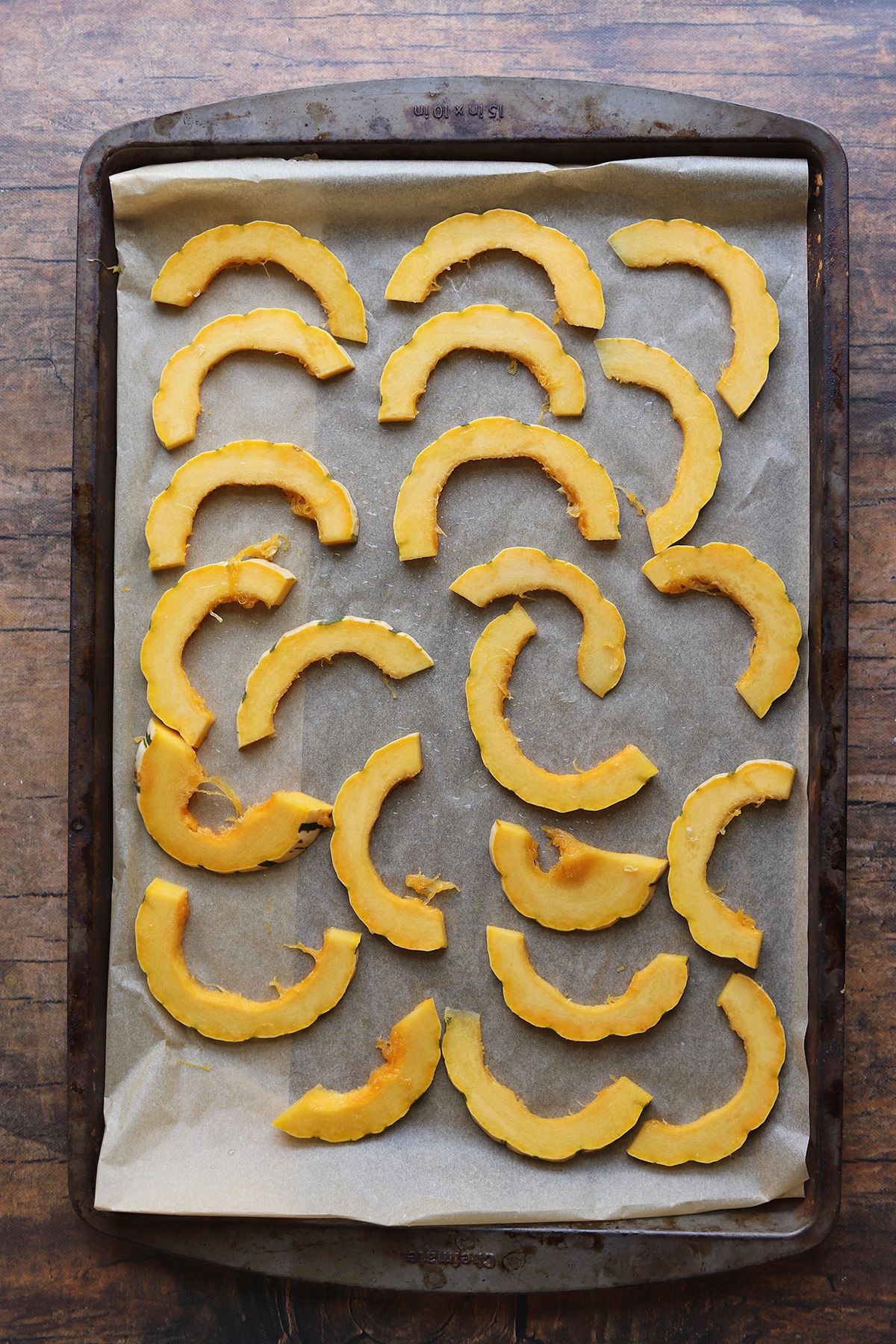Sliced delicata squash on baking sheet.