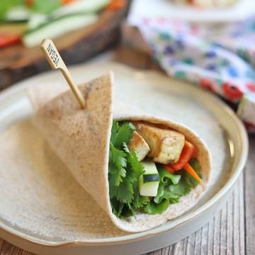Tortilla wrap on plate, filled with tofu and vegetables.