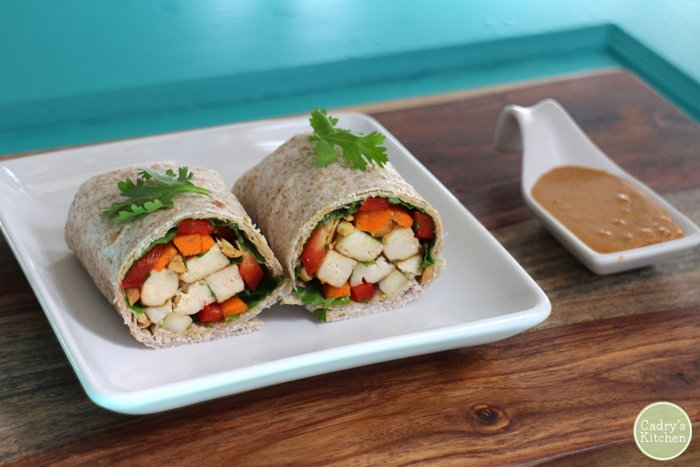 Spring roll wraps with baked tofu and peanut sauce on plate.