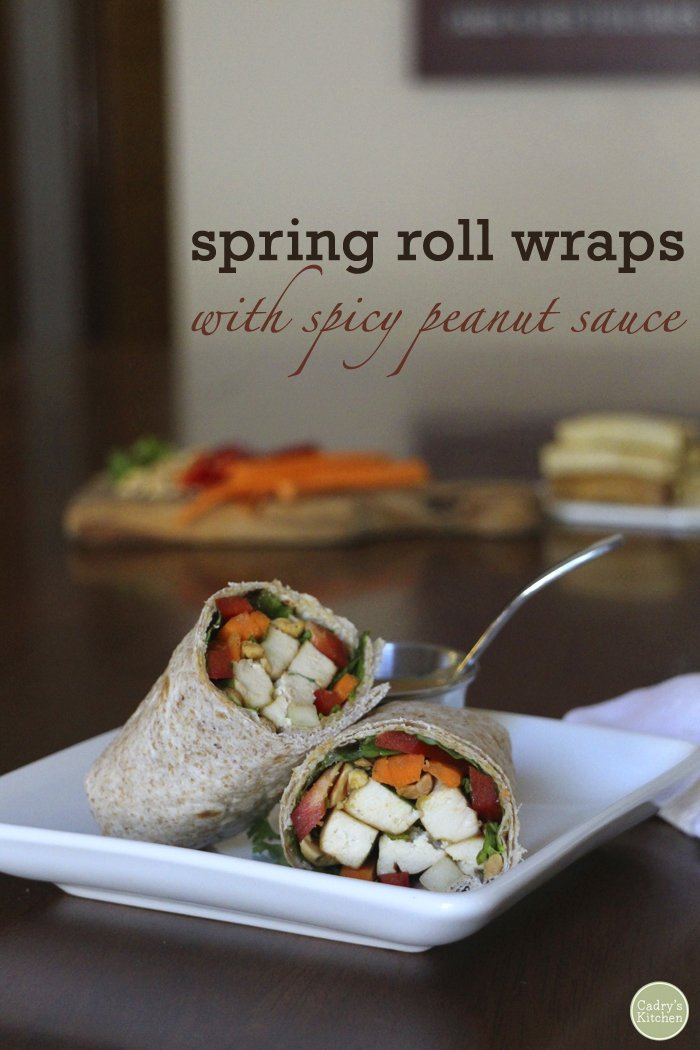 Text overlay: Spring roll wraps with spicy peanut sauce. Wraps on table with cup of sauce.