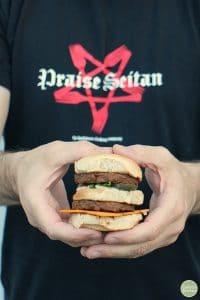 Hands holding a vegan Big Mac slider.