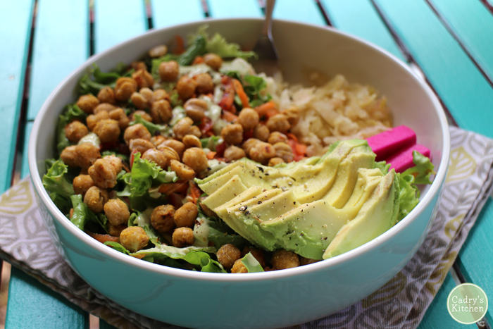 Salad with roasted chickpeas, avocado slices, and sauerkraut in bowl.
