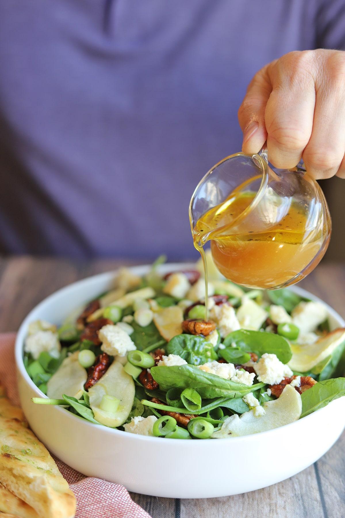 Apple cider vinaigrette being poured onto salad.