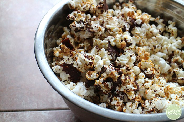 Popcorn in metal bowl, tossed with chocolate and peanut butter sauce.