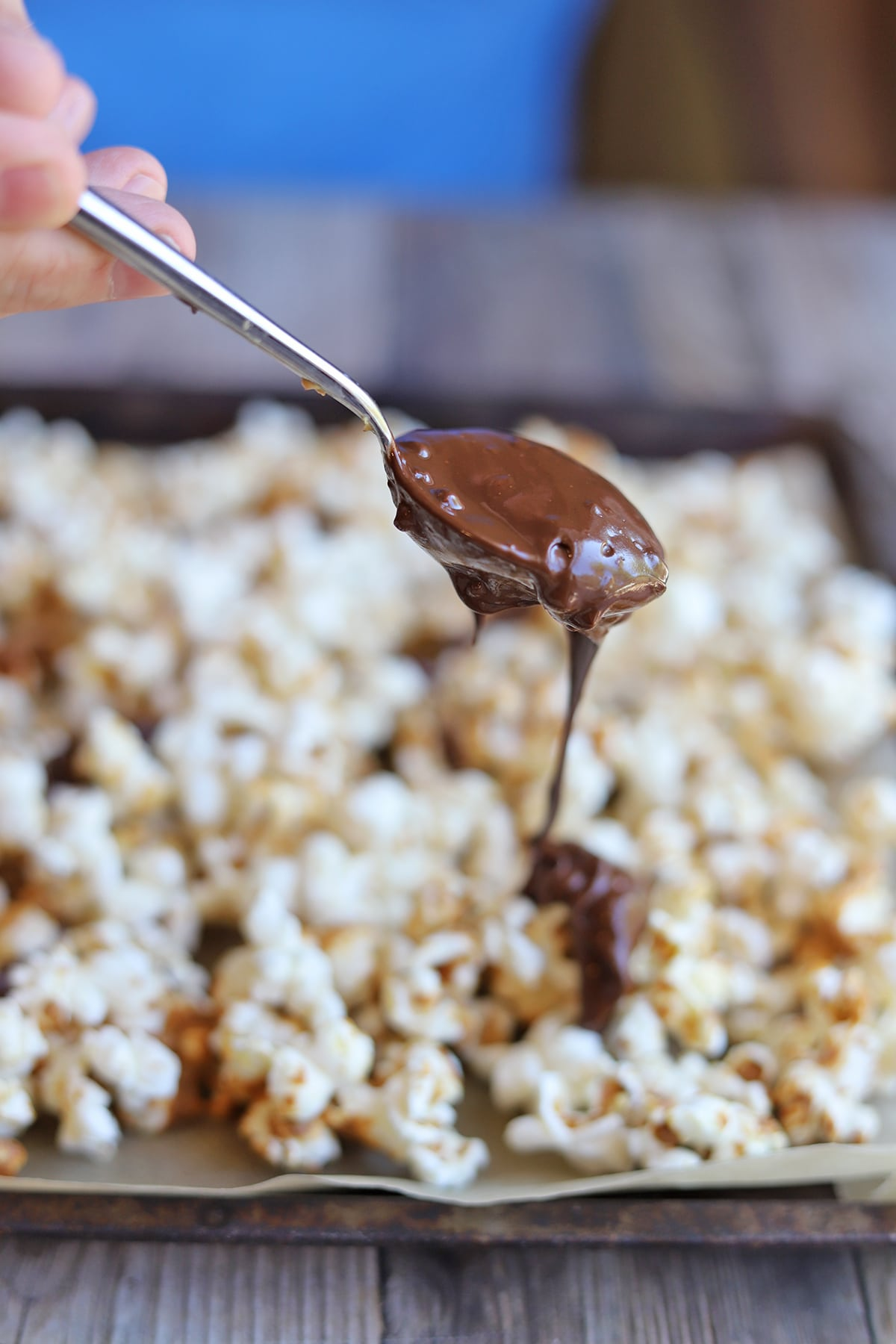 Spoon drizzling melted chocolate onto popcorn.