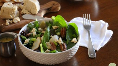 Leafy spinach in a bowl with candied pecans, tofu chevre, and roasted apples.