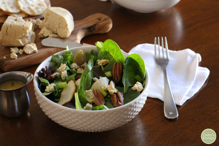 Fall salad with apples and candied pecans in white bowl. In background, tofu chevre on cutting board.