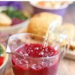 Text overlay: Orange cranberry sauce. Vegan and gluten-free. Sauce in glass container on table with holiday dinner.