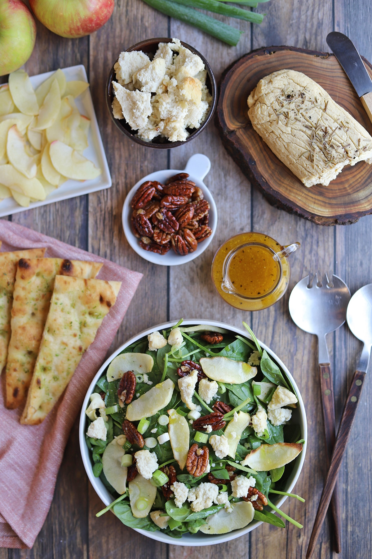 Overhead table with salad, toasted bread, candied pecans, and baked apple slices.