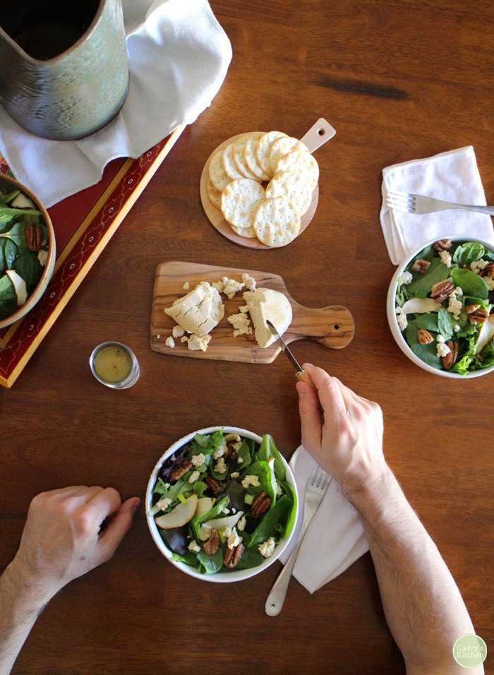 Overhead hands slicing into tofu chevre. Bowls of salad with apples, candied pecans, and cider vinaigrette.