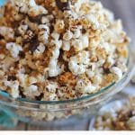 Text overlay: Peanut butter and chocolate popcorn. Flavored popcorn in clear bowl.