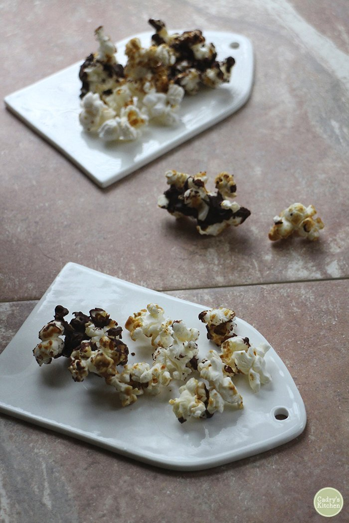 Little plates with peanut butter and chocolate covered popcorn on them.
