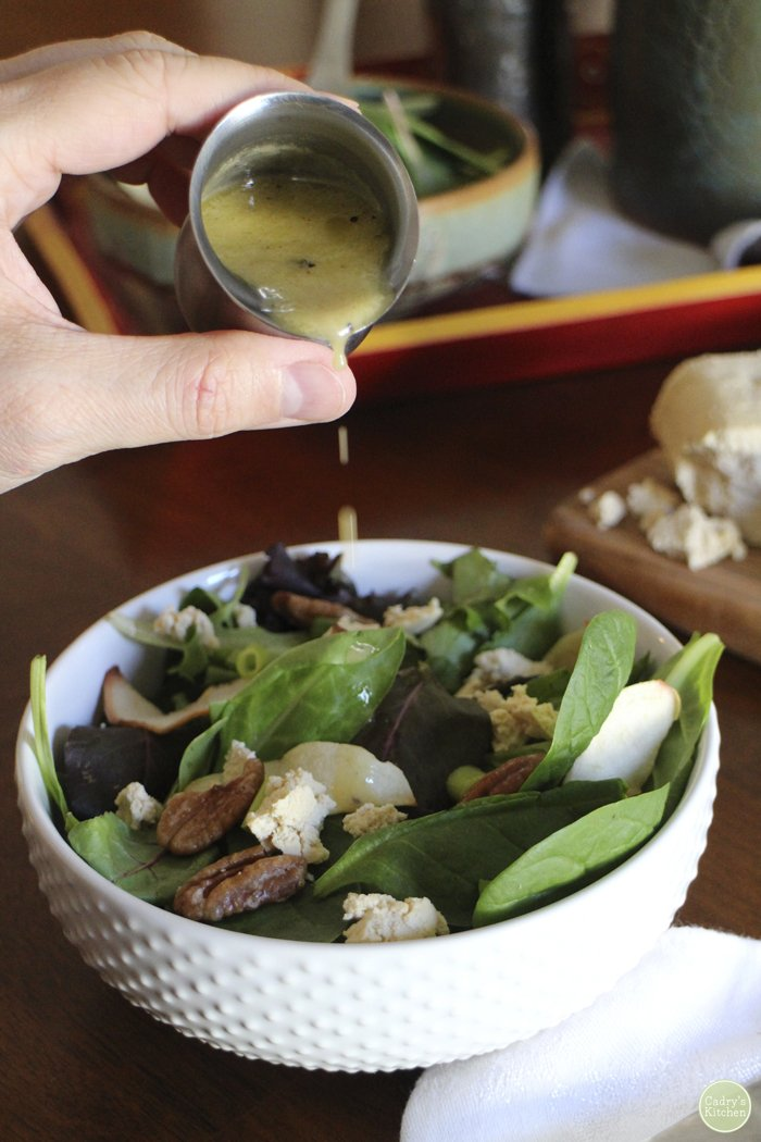 Hand pouring cider vinaigrette onto salad with apples and candied pecans.