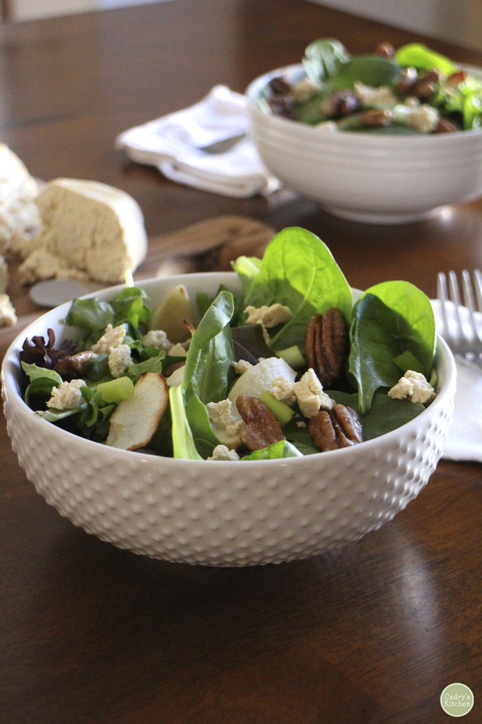 Fall salad with apples & candied pecans in white bowl. Tofu chevre in background on table.