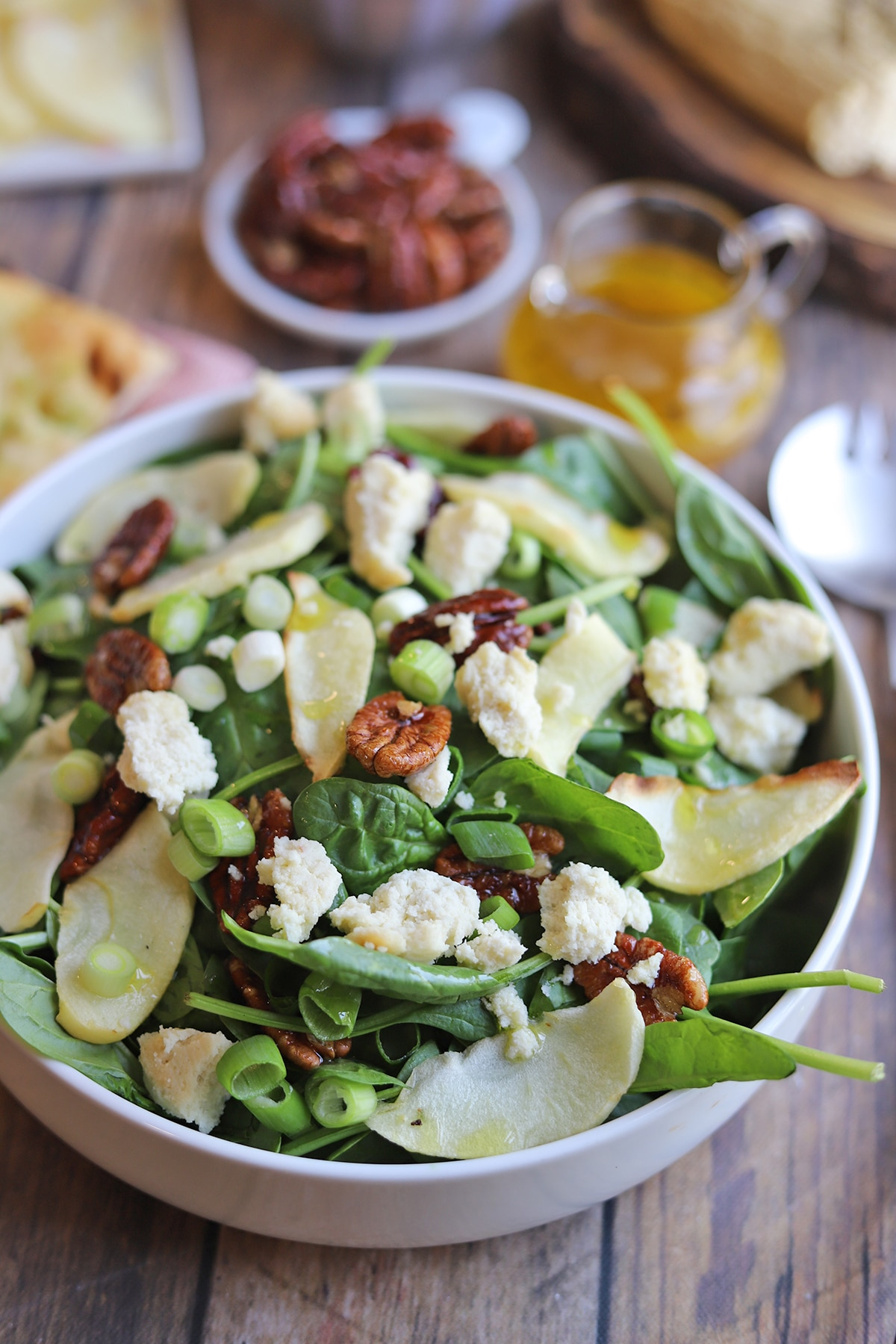 Close-up roasted apple salad with candied pecans and vegan feta.