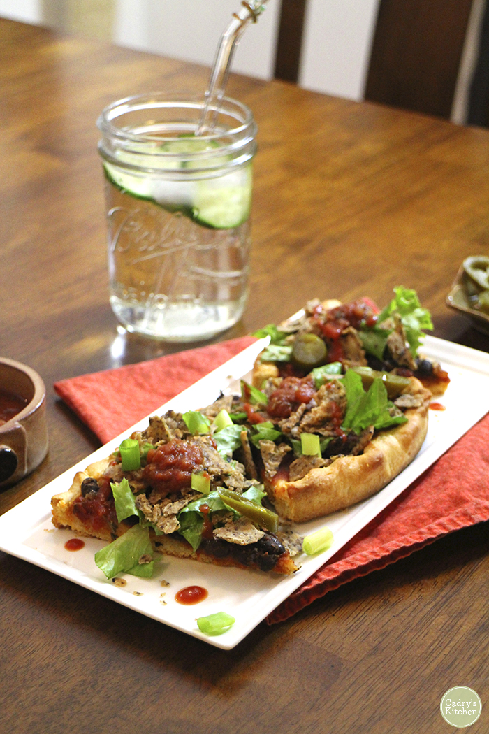 Taco pizza slices on plate with cucumber water.