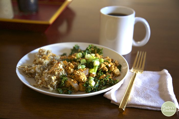 Tofu scramble on plate with hash browns. Coffee cup in background.