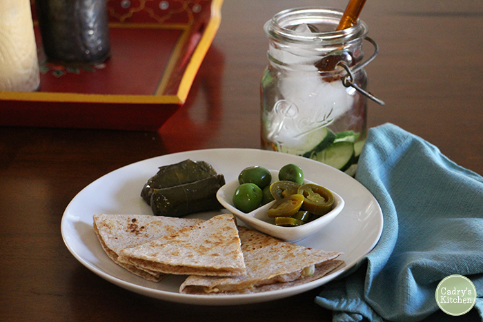 Toasted tortilla on plate with dolmas, Castelvetrano olives, and jalapeno peppers.